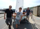 (L-R) Tim Price and Tom Trevessey and boat owner Lachlan McKenzie in the background - bringing 14' 'Tailwind' Yachting World Day Boat to the harbour